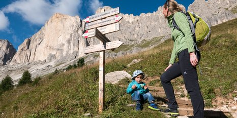 Hike parents mother child Catinaccio with signpost