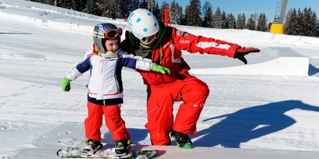Skischool Carezza Sknowboardlehrer mit Kind