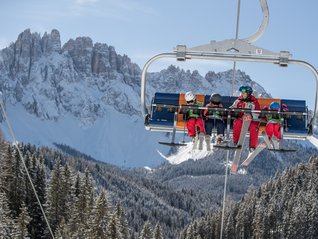 Skischool Carezza instructor with newbies in the chairlift Tschein