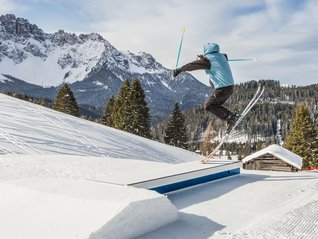 Snowpark Carezza jump of a skier with Tschein lift